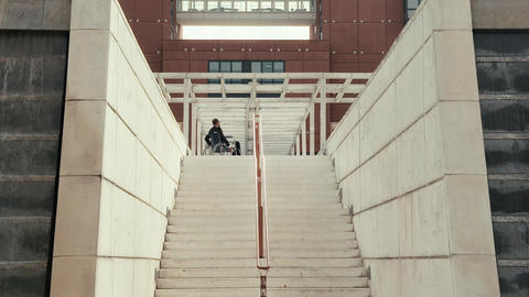 Businessman on wheelchair moving back from stairs Footage