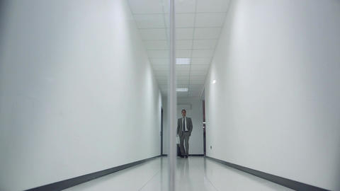 Businessman carrying suitcase in office corridor Stock Video Footage