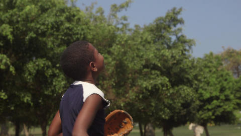 Happy black child playing baseball in park Footage