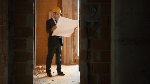 Architect Standing in House Under Construction with building plans Footage