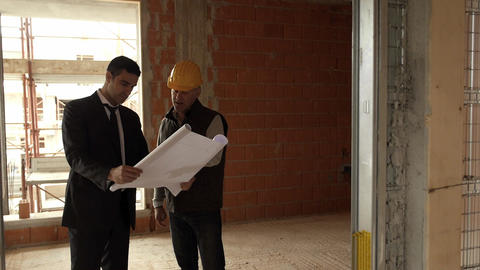 Plumber and Architect Talking and Looking at Blueprint Stock Video Footage
