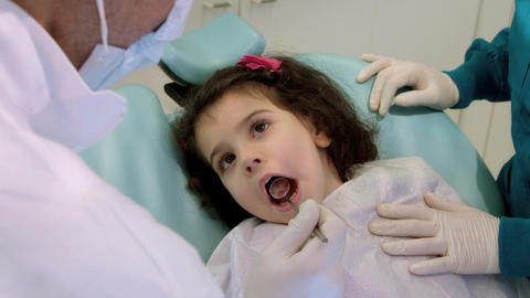 Dentist and Assistant Checking Teeth of Young Girl Stock Video Footage
