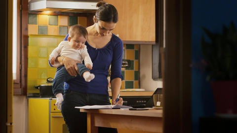 Multitasking Mother Cooking and Working Holding Little child Stock Video Footage