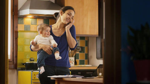 Multitasking Mother Cooking and Working Holding Little child Footage