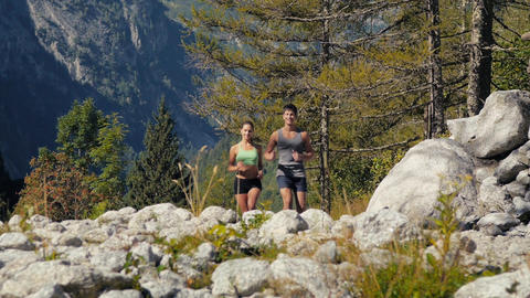 1of 4 Man And Woman Running On Mountain Path stock footage