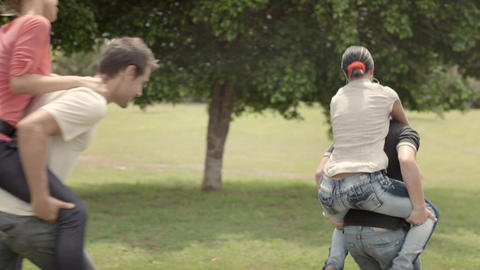 Young Couples Running Piggyback in Park Stock Video Footage