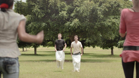 Young Men Playing Sack Race in Park Stock Video Footage