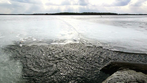 High wind moving water between ice and a rocky sho Stock Video Footage