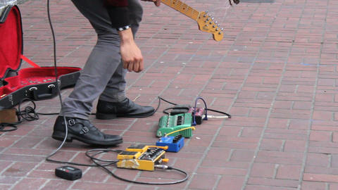 Sidewalk Busker Guitarist Adjusting His Foot Pedal stock footage