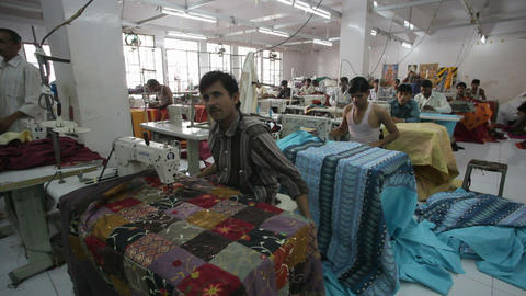 Men Working In Garment Factory Sewing At Machines, stock footage