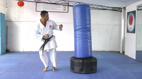 Black belt karate practicing kicking the sandbag Footage