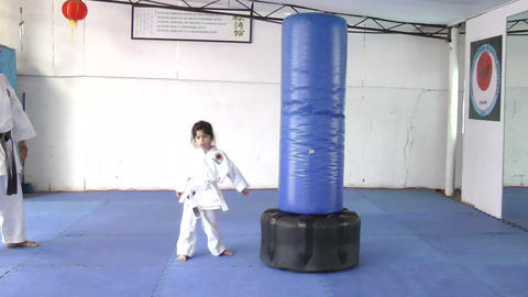 Little girl practicing kicks with the sandbag Footage