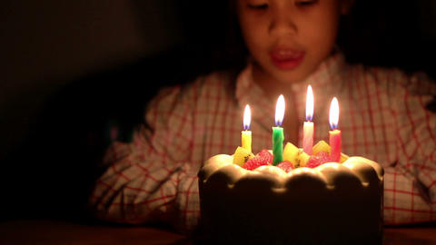Asian girl blowing birthday cake candles Live Action