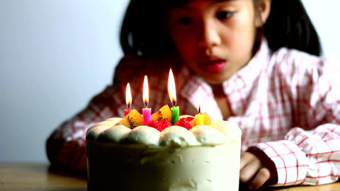 Asian girl blowing birthday cake candles Footage