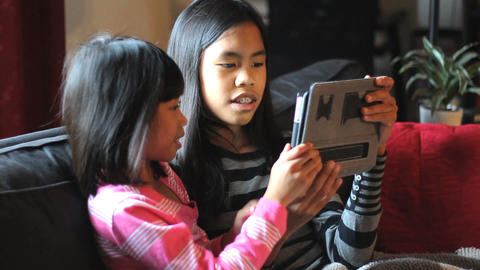 Asian Sisters Playing Games On Tablet Together Footage