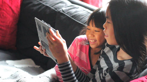 Asian Sisters Spending Time Together On Tablet Footage
