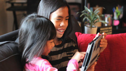 Cute Little Asian Girls Playing Game On New Tablet Footage
