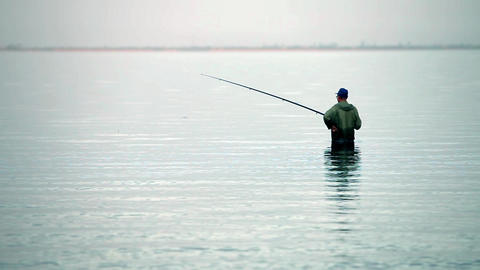 fisherman with rod in the water fishes Footage