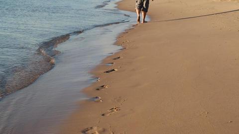 feet of man walking along edge of sea leave footpr Footage