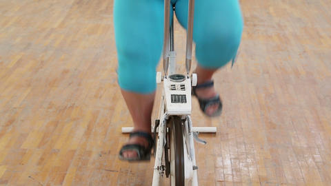 Overweight Woman Exercising Legs On Bike Simulator stock footage