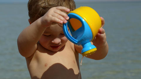 Little boy having fun with toy waterpot Footage