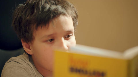Young boy concentrating on reading a book Footage