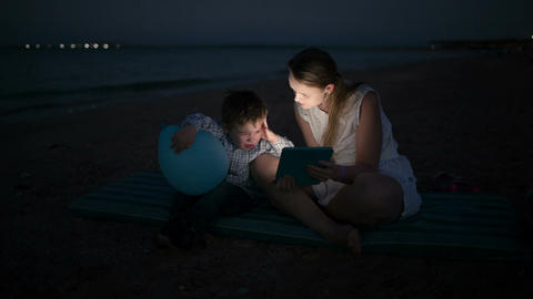 Mother And Son With Pad By The Sea At Night stock footage