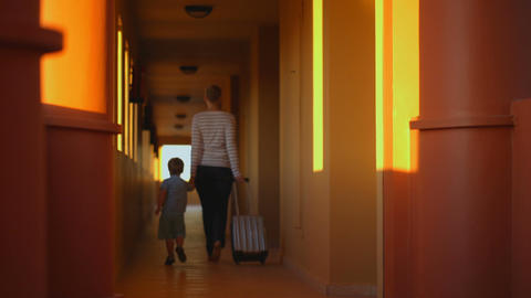 Mother with son leaving the hotel Footage