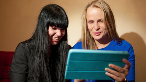 Two young woman reading a tablet-pc Footage