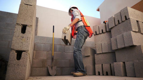 Woman Lifts Brick On Construction Site stock footage