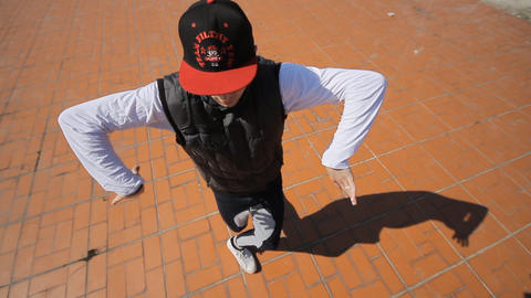 Hip-hop dancer in cap dances in the street of Sara Footage