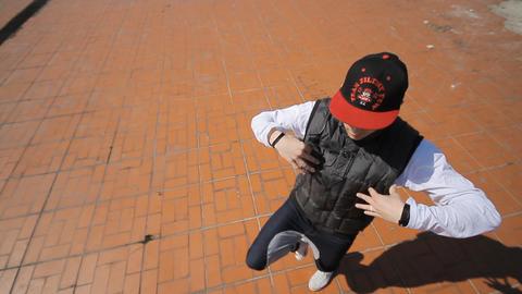 Hip-hop dancer in cap dances in the street of Sara Footage