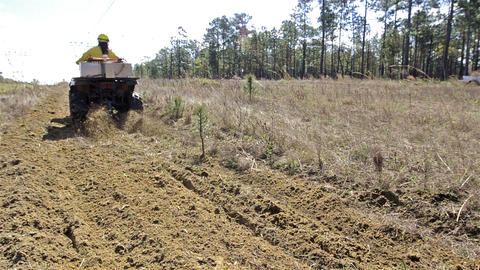 A crew member grading a fire break with an ATV alo Live Action