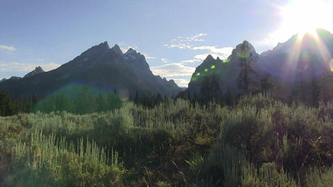 Pan across the sun peeking above the Grand Tetons  Footage