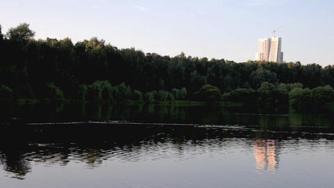 Evening in park, lake, mirror with building at background Stock Video Footage