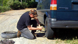 Man Changing Tire On Dirt Road Part 4 stock footage
