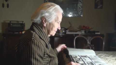 Old Lady Going Through Family Photos Side-Shot Footage