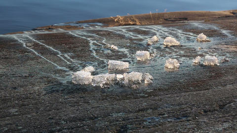 Pieces of ice melting on a lakeside rock Footage