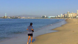 Middle Aged Man Jogging Down Urban Beach stock footage