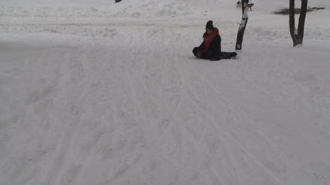 Two Young Females Sliding On A Slope Having Fun Footage