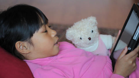 Asian Girl Reads Story To Teddy Bear Using Tablet stock footage