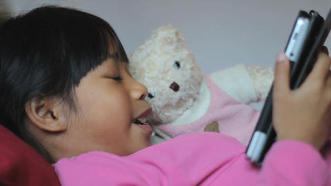 Close Up Little Girl Reads Book To Stuffed Bear Footage