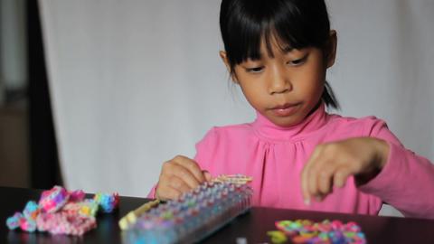 Cute Girl Making Colorful Bracelet On Loom Footage