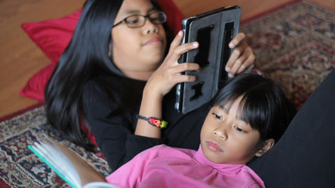 Girl Reads Book While Sister Plays Game On Tablet Footage