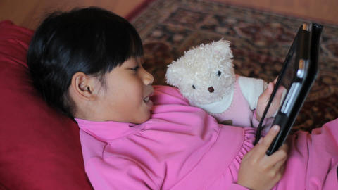 Asian Girl Reading To Her Teddy Bear With Tablet Footage