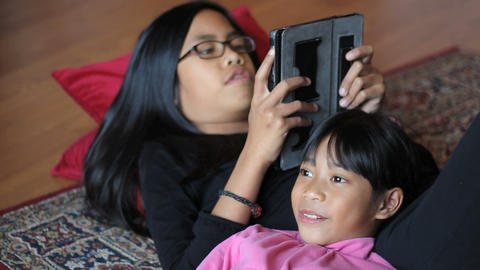 Little Girl Enjoys Story From Big Sister On Tablet Footage