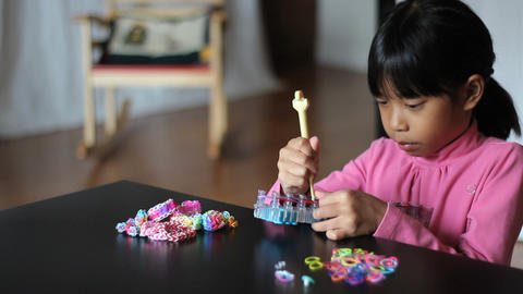 Girl Patiently Uses Her Loom To Make Bracelet Footage