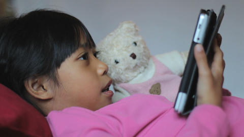 Little Girl Reads Book To Teddy Bear Using Tablet stock footage