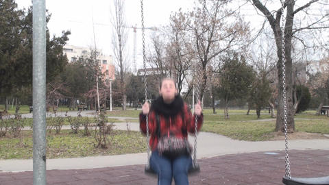Young Female Swings In A Park Front-Shot Footage