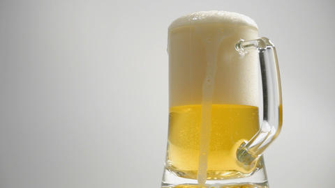 Pour the beer into a glass on a white background Footage